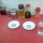 永楽 そば店 - お冷やと餃子用の小皿、その奥には手作りラー油ー湯?などの定番の香辛料