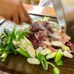 スタミナとん - スタッフによって調理中のとん焼き。客はじっと見ているだけ。