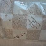 餅工房 おくやま - 包み紙。雁月、あん餅、おこわなどの字が見られます。