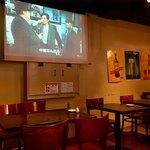 アンガスプライム牛ステーキと創作オムライス Beer House KISH - 店内風景。スクリーンには映画が映っている(音声なし)。