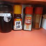 三陽軒 - 「三陽軒」卓上のソース・ラー油・コショウ・一味