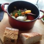 86781496 - 【ココット料理c.】野菜とソーセージとベーコンの香草焼きとセットのパン(接写)