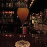 バースカーレット - シャンパンと生のパッションフルーツと清美オレンジのカクテル、グラスはバレリーナ