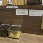 サバ6製麺所 - だし割の案内、ニラ唐辛子・一味・キザミニンニク・こしょうの薬味の案内、紙エプロン
