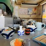 楽ちゃん - 店内の様子。卓上には漬物、大根おろし、ダシ醤油などが用意されています。
