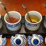 ガイ - ガイ @宝町 タイの食卓4大調味料 右からナンプラー(魚醤)・ナムソム(酢)・プリックポン(乾燥唐辛子)・ナムターン(砂糖)