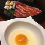 焼肉門門 - 雲丹手毬寿司をサーロインで包み卵に潜らせていただきます。卵からのショット。