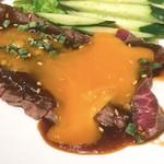 ニクヤキ ギンキョウ - 牛モモ肉のスーパーレアステーキ ユッケ風味の黄身を潰しました。