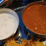 DELHI GATE - 右は肉がソース内にコロコロ入っているピリ辛「ラムカレー」、左は「ライタ」というヨーグルトサラダ