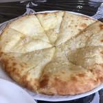デリパレス - チーズナンのアップ。白いつぶつぶはココナッツ