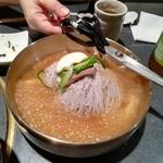 90940745 - 手打ちのモチモチ麺をハサミで切って頂きます