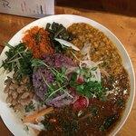91189026 - デフォのカレー、豆カレー、人参と大根のマリネ、水菜?赤い粉末?あさりカレーと玉ねぎ、真ん中の雑穀米にカイワレ