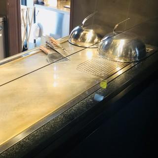 オープンキッチンの鉄板で焼き上げる肉料理の数々