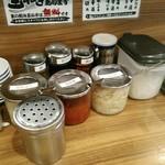 横浜家系ラーメン 町田商店 マックス - 生姜、玉葱、きゅうちゃん、白ごま、豆板醤、にんにく、ラー油、酢などテーブルの上が賑やか。