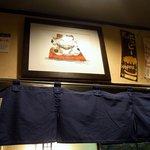江戸幸 - カウンター席から頭上を撮りました。 ここにも暖簾が掛かっていましたよ。 入口の暖簾と同じような感じになっています。 濃紺地に、江戸幸って書いていますね。 そして、その暖簾の上には、猫ちゃんが鎮座してい