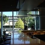 ピエール・エルメ・パリ - カウンターキッチンと緑が見える2階席