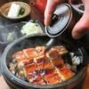 うなぎ料理江戸川 - 料理写真:王道?!新感覚?!「鰻石焼きまぶし」  うなぎ料理の定番、「おひつまぶし」が進化した!「おひつ」ではなく「石焼き鍋」で食す、ひつまぶし。その名は「鰻石焼きまぶし」。あつあつの石鍋に、うなぎのタレをかけてときに立ち上る、香ばしい香りがたまらない。オコゲや、ダシを加えて雑炊風にしたりと、楽しみ方は千差万別。ぜひご賞味ください。3400円(税込)