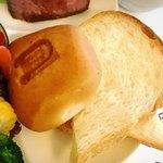 トアロード・デリカテッセン - お店のロゴが入った熱々の丸いパンと、バターが塗られた食パン