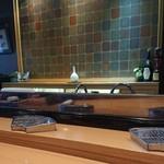 千成 - カウンター。この扇型の金網に揚げたて天ぷらが来ます。奥に小さく見えるモノクロ写真が気になりました。