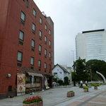 9356801 - 左側の赤い建物の一階が店舗です。右の建物は高崎市役所