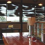麺屋ラ賊 - 厨房を囲むL字カウンター席と、窓際の小上がり。