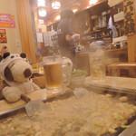 六文銭 - じゅ~じゅ~  ビールとウーロン茶を飲みながら、 もんじゃが焼けるのをのんびり待つボキら。 いいにおいです。