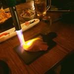 97618969 - お通しの炙り寿司を炙ってます