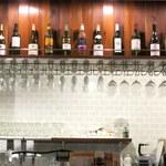 浅草グリルバーグ - カウンター席の上にはボトルとグラスが並んでいます。