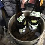 久村の酒場 - ストーブで一升瓶ごと燗します。