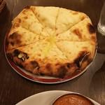 ネパール・インド料理 Happy - +300円で変更できるチーズナン♪奥のお手拭きと大きさを比べるとどれだけ大きいか分かるかな?生地にチーズがぎっしり練り込まれていて超美味しいです♪
